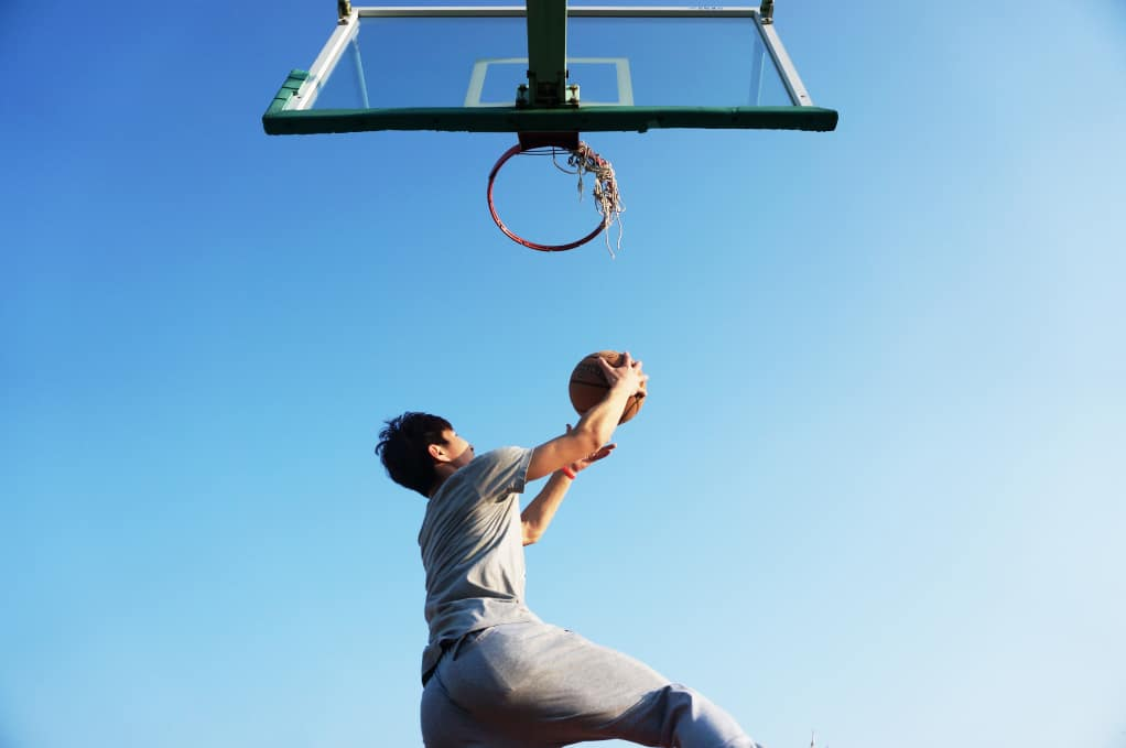 Athlete reaching up to throw a basketball in the hoop